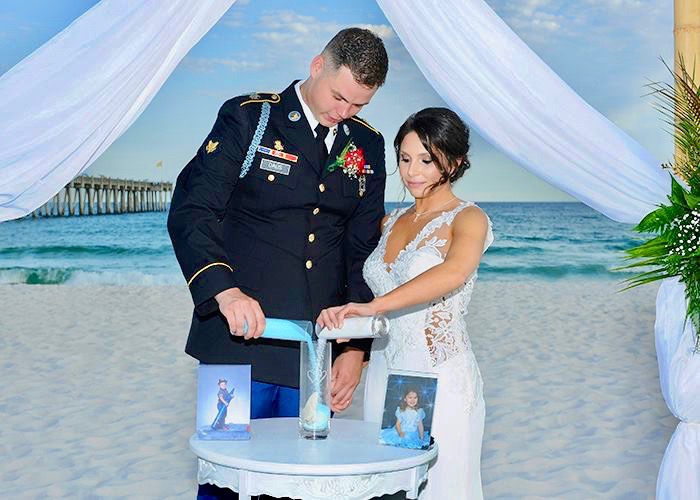 Bride and groom on the beach pouring sand