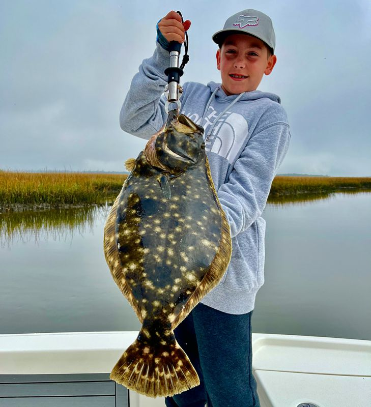 Young Boy Holding A Flounder