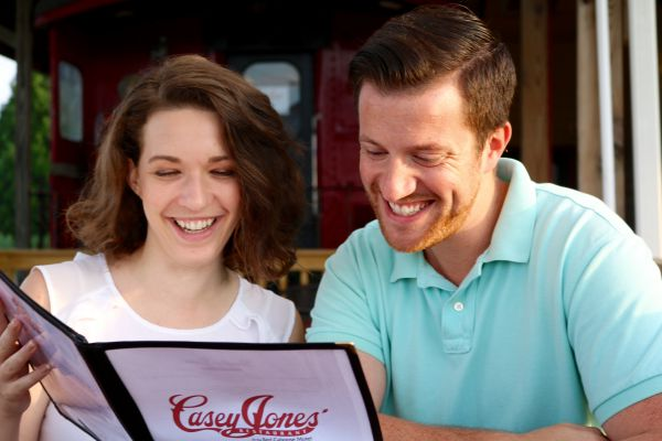 young couple reading restaurant menu together at table