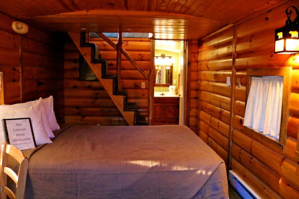 interior of wooden caboose with big bed in the middle