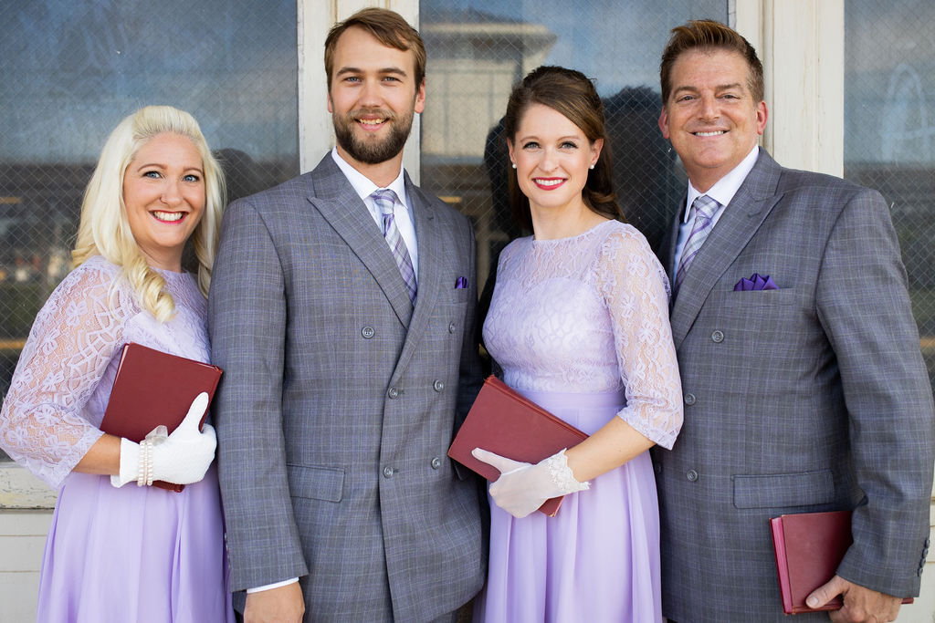 men and women in concert attire holding hymnals