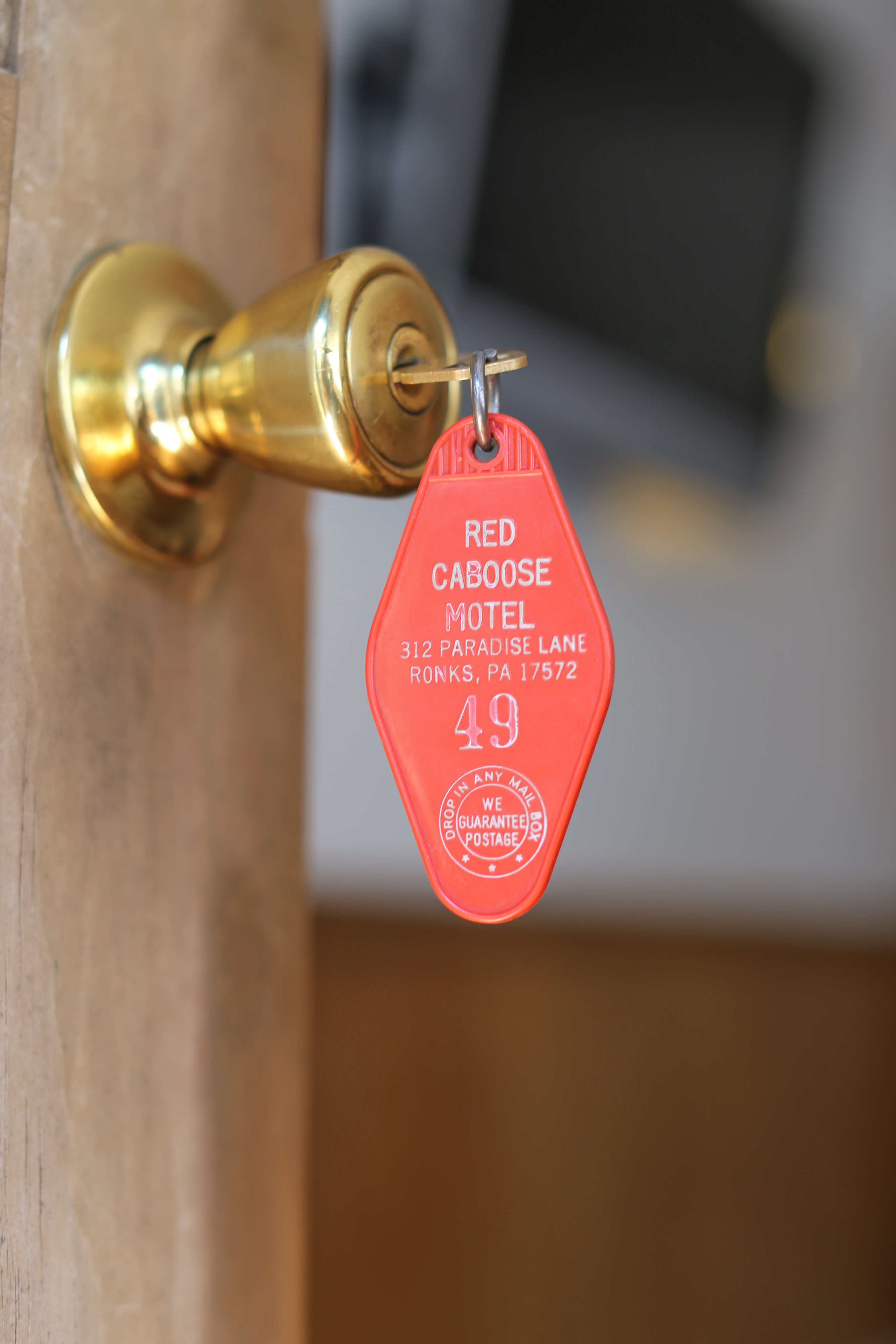 open motel door with key in lock featuring red motel key chain
