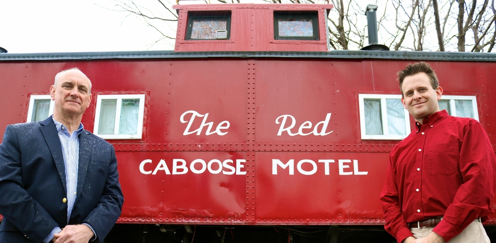 father and son owners standing in front of Red Caboose Motel sign