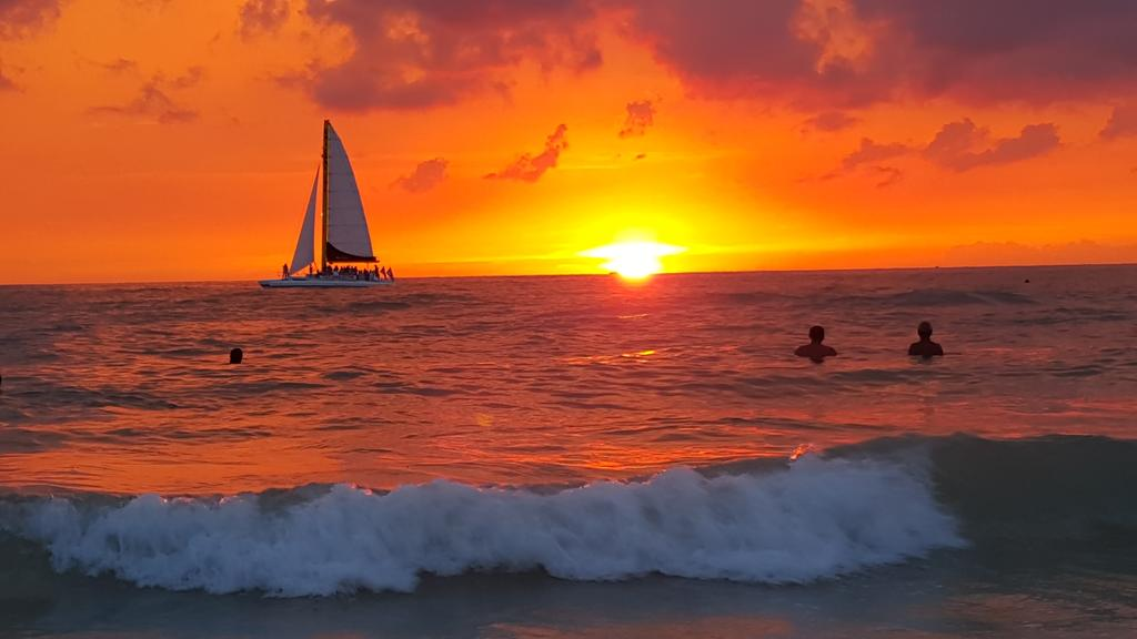 sunset with people swimming and sailboat in distance