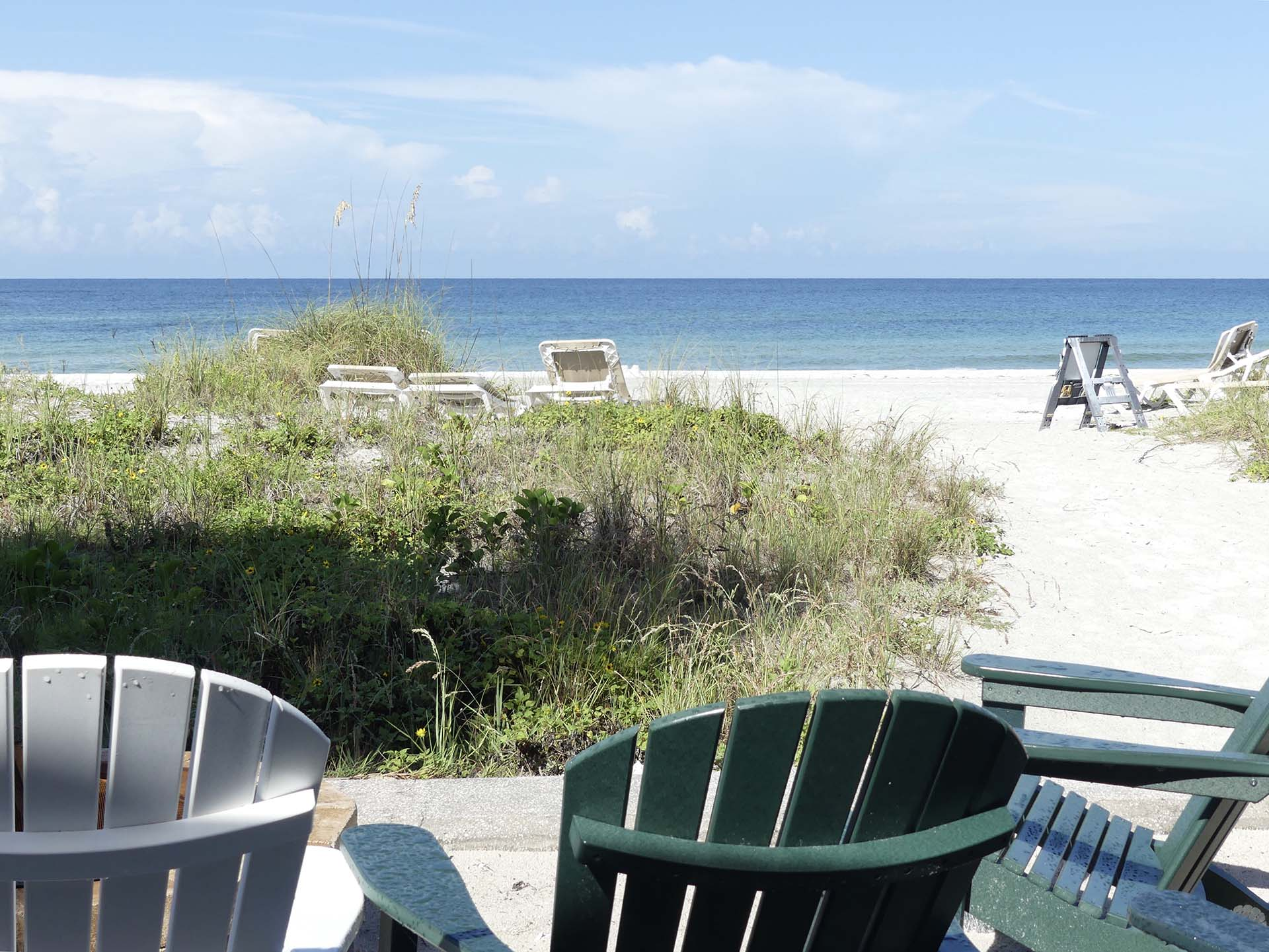 adirondack chairs facing the dunes and beach