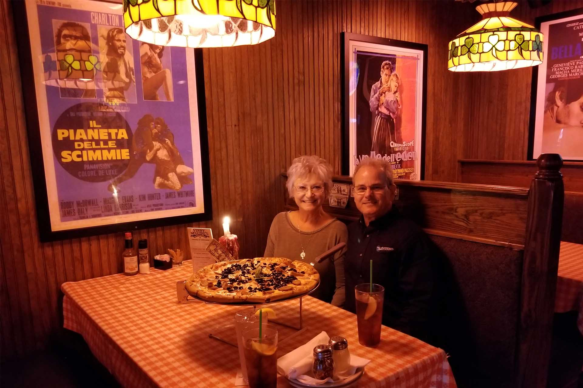 smiling couple sitting at restaurant table with large pizza in front of them