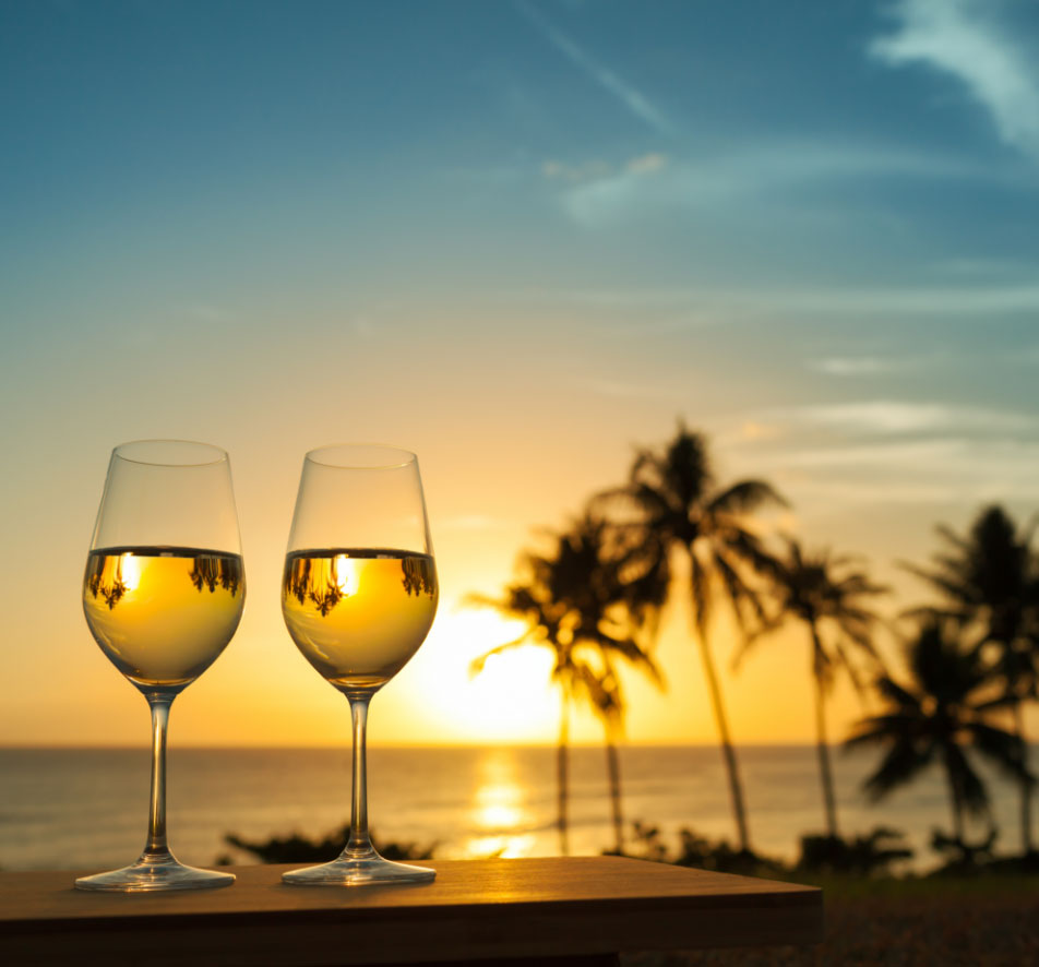 Two wine glasses on a railing overlooking the ocean