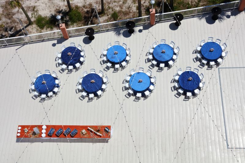 aerial view of outdoor deck featuring tables with blue tablecloths