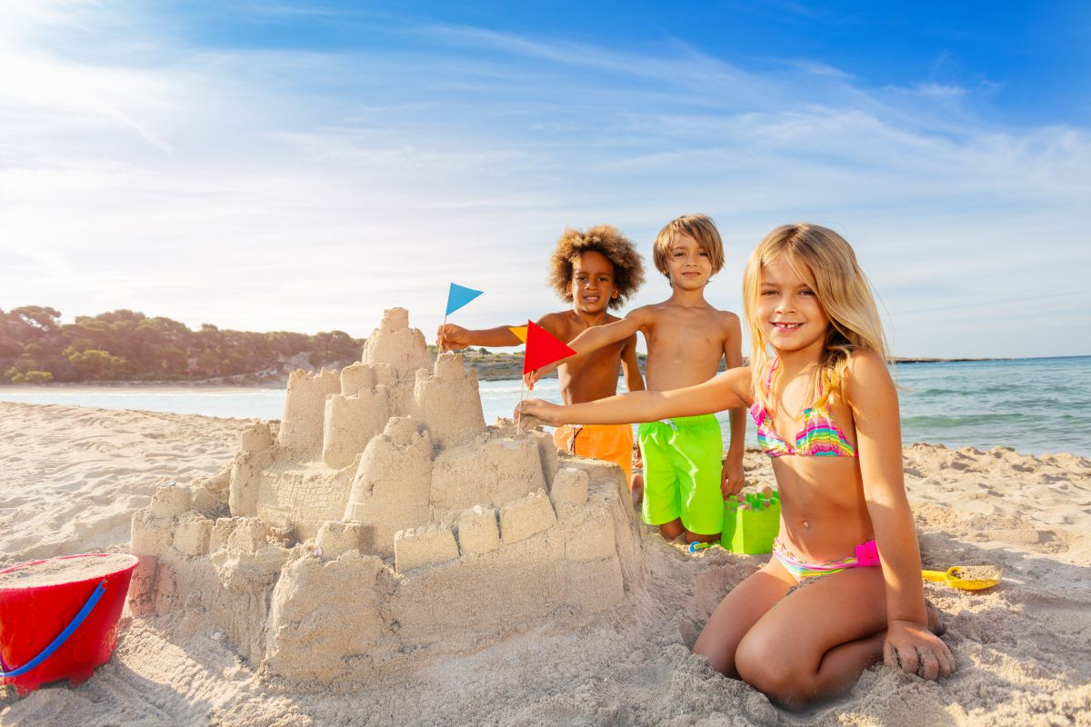 group of young kinds building a sand castle on beach