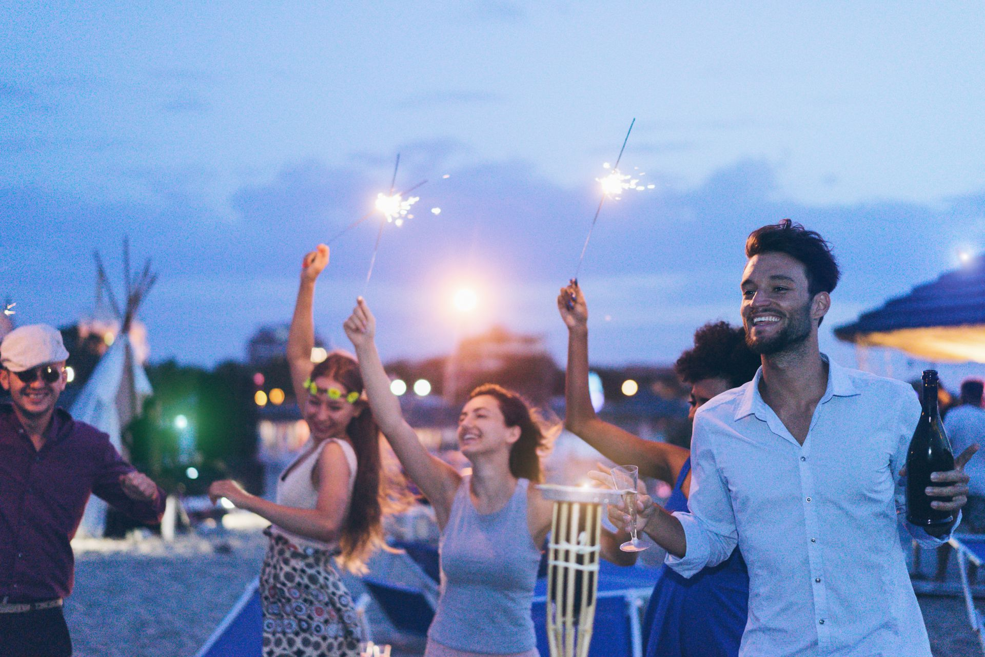 group of young adults drinking on beach holding sparklers