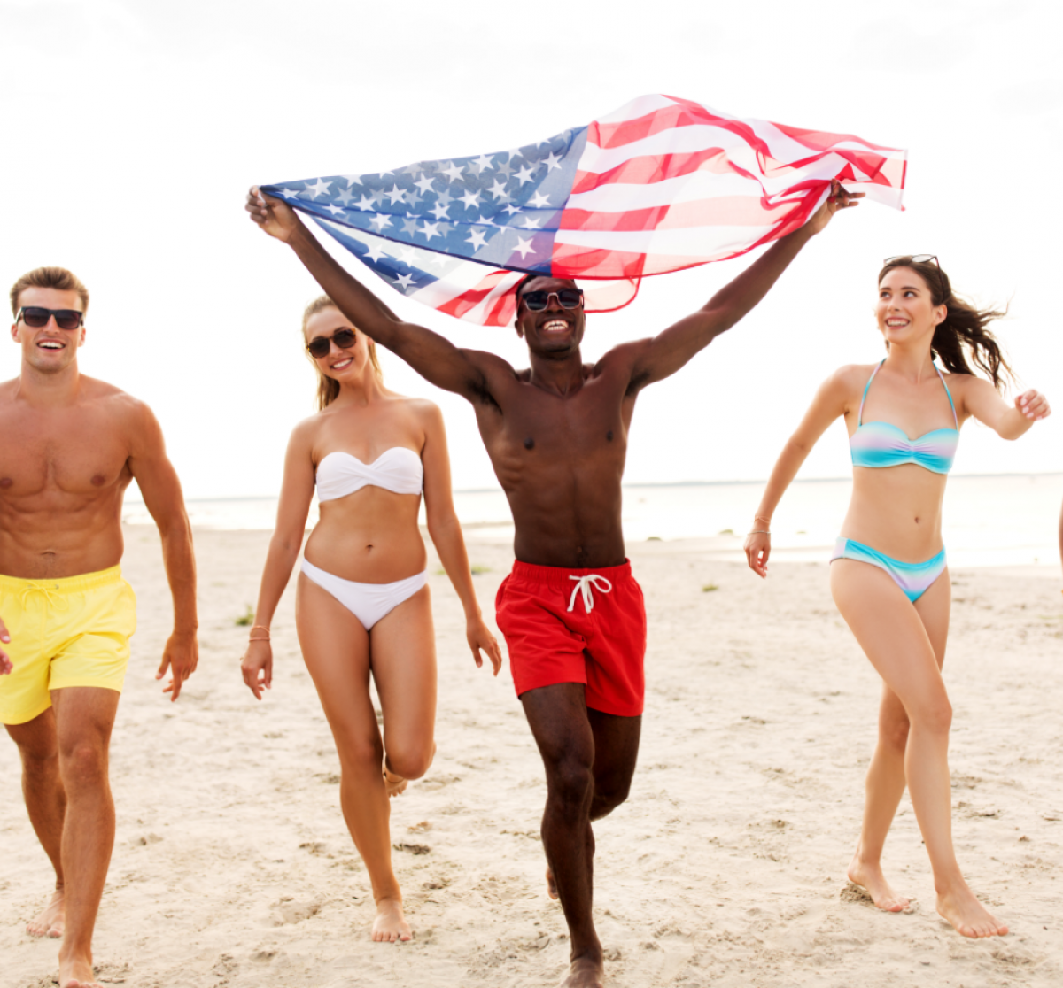 man carrying american flag waving on beach with friends