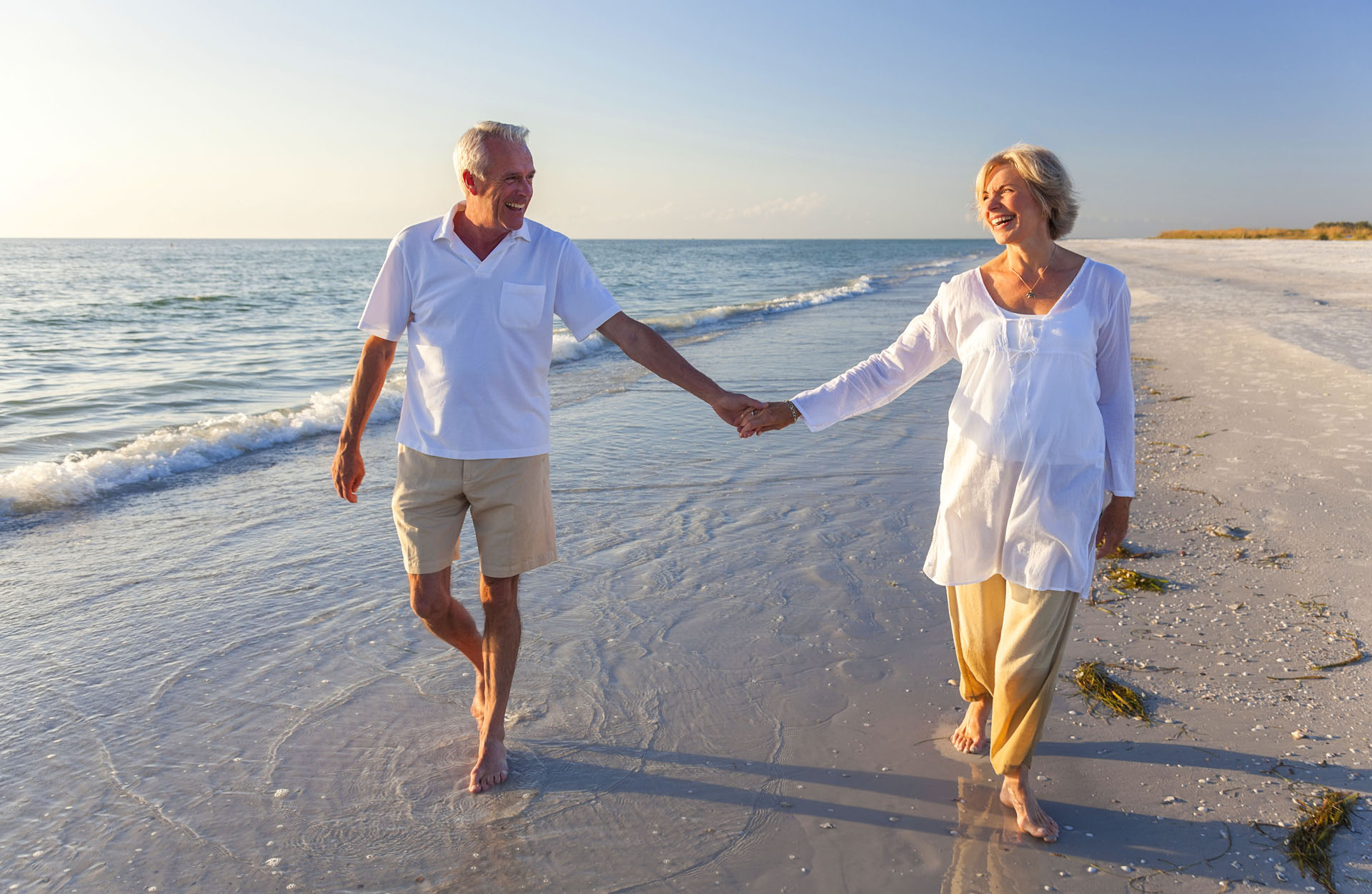 a senior couple in white walking on the beach