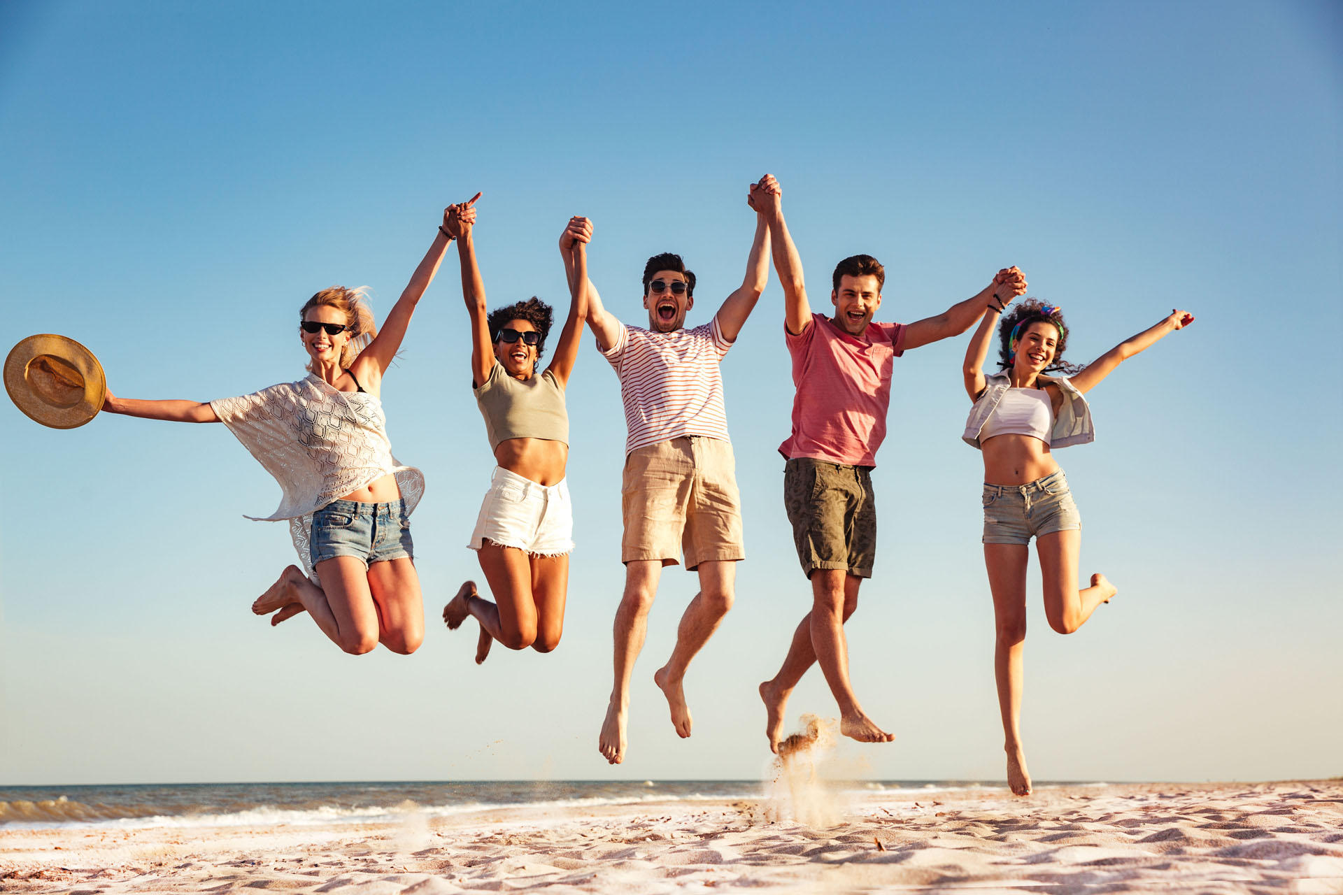 group of five young adults jumping together on beach