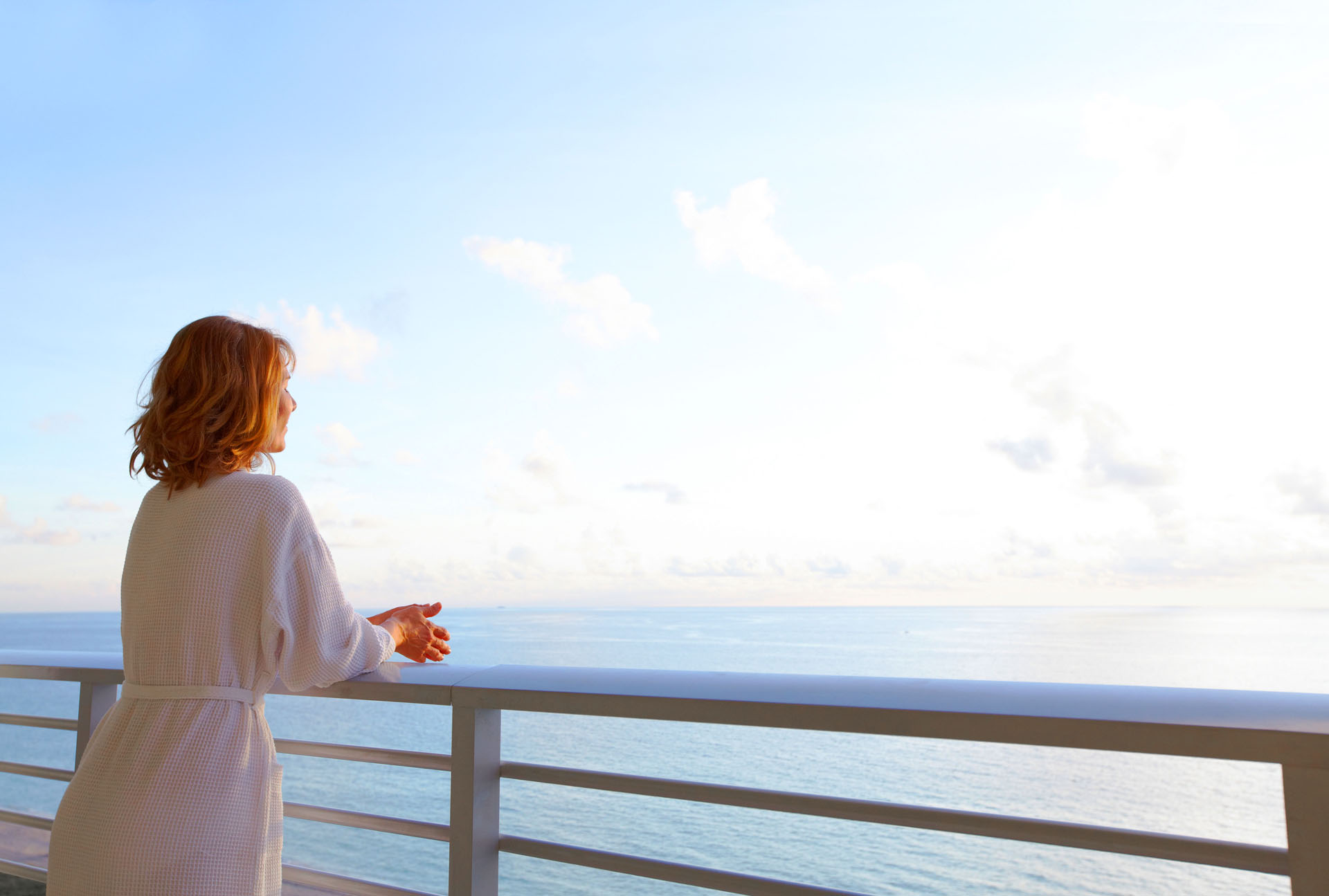 woman in bathrobe looking out to the water from patio