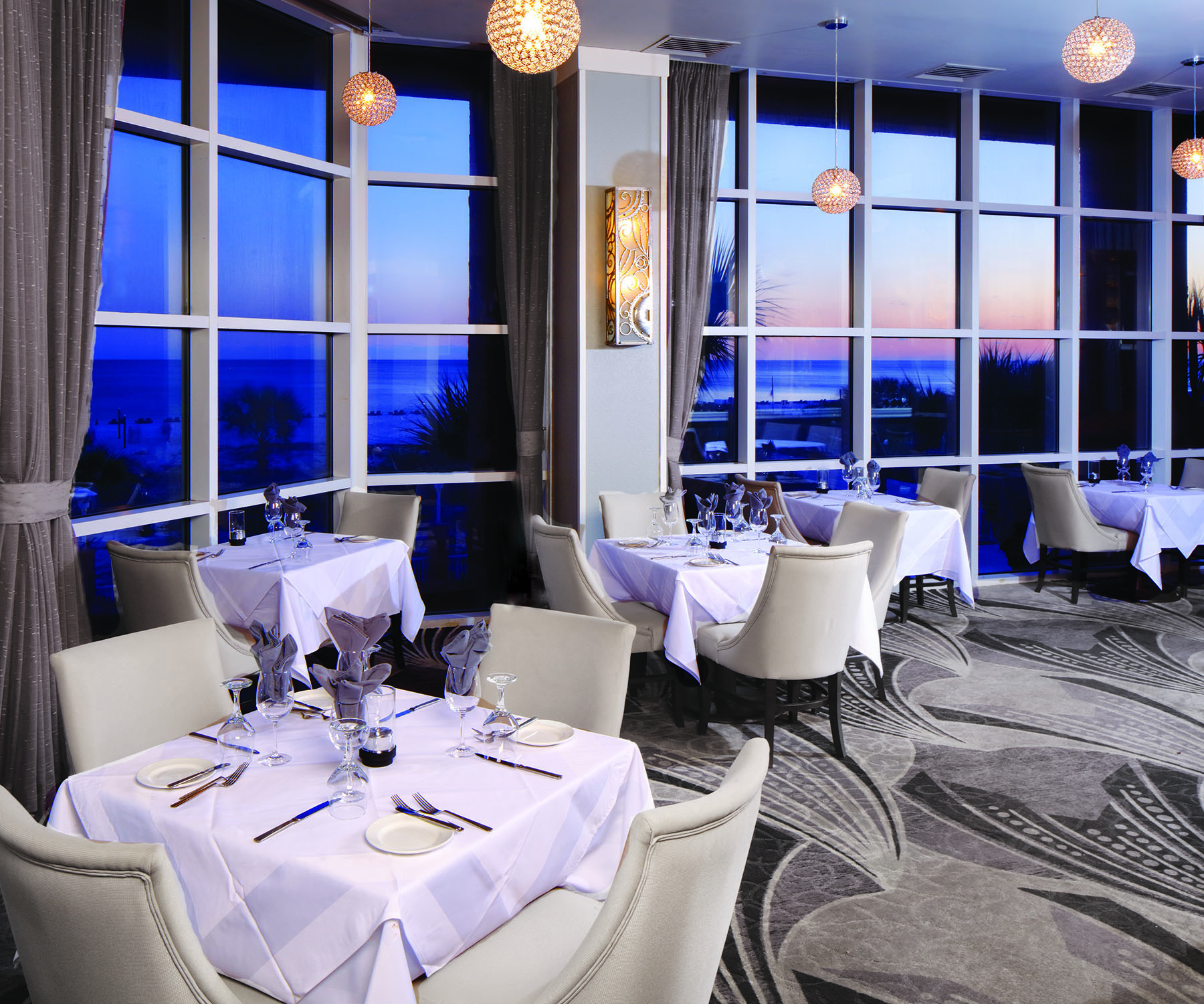 restaurant dining room with large windows overlooking evening at beach