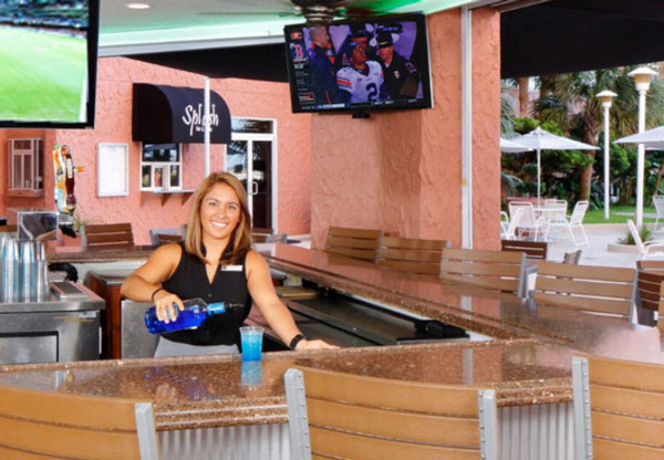 smiling bartender pouring drink at bar