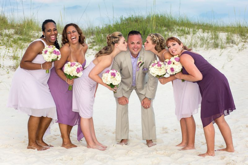 groom surrounded by group of laughing bridesmaids on beach