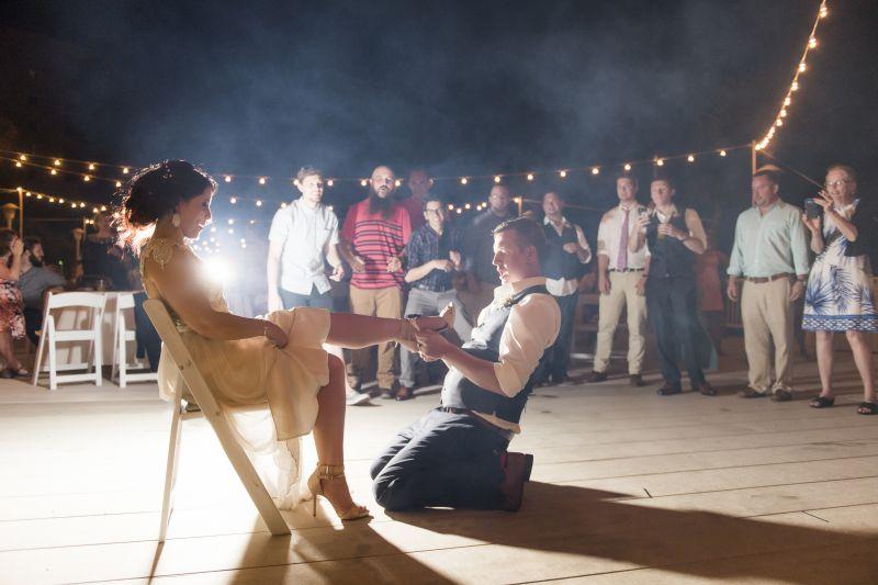 groom removing garter belt from bride's leg at night