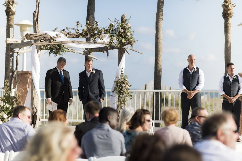 groomsmen standing at outdoor beach altar surrounded by guests