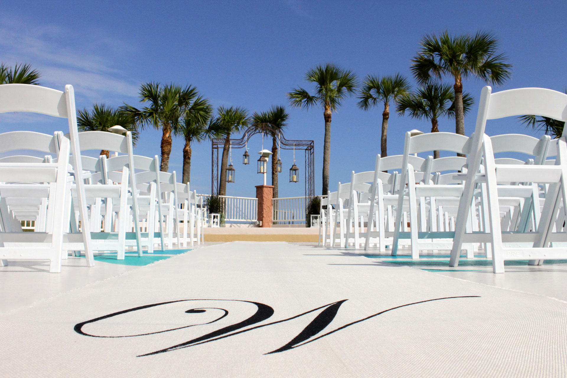 rows of outdoor wedding chairs in front of beach altar