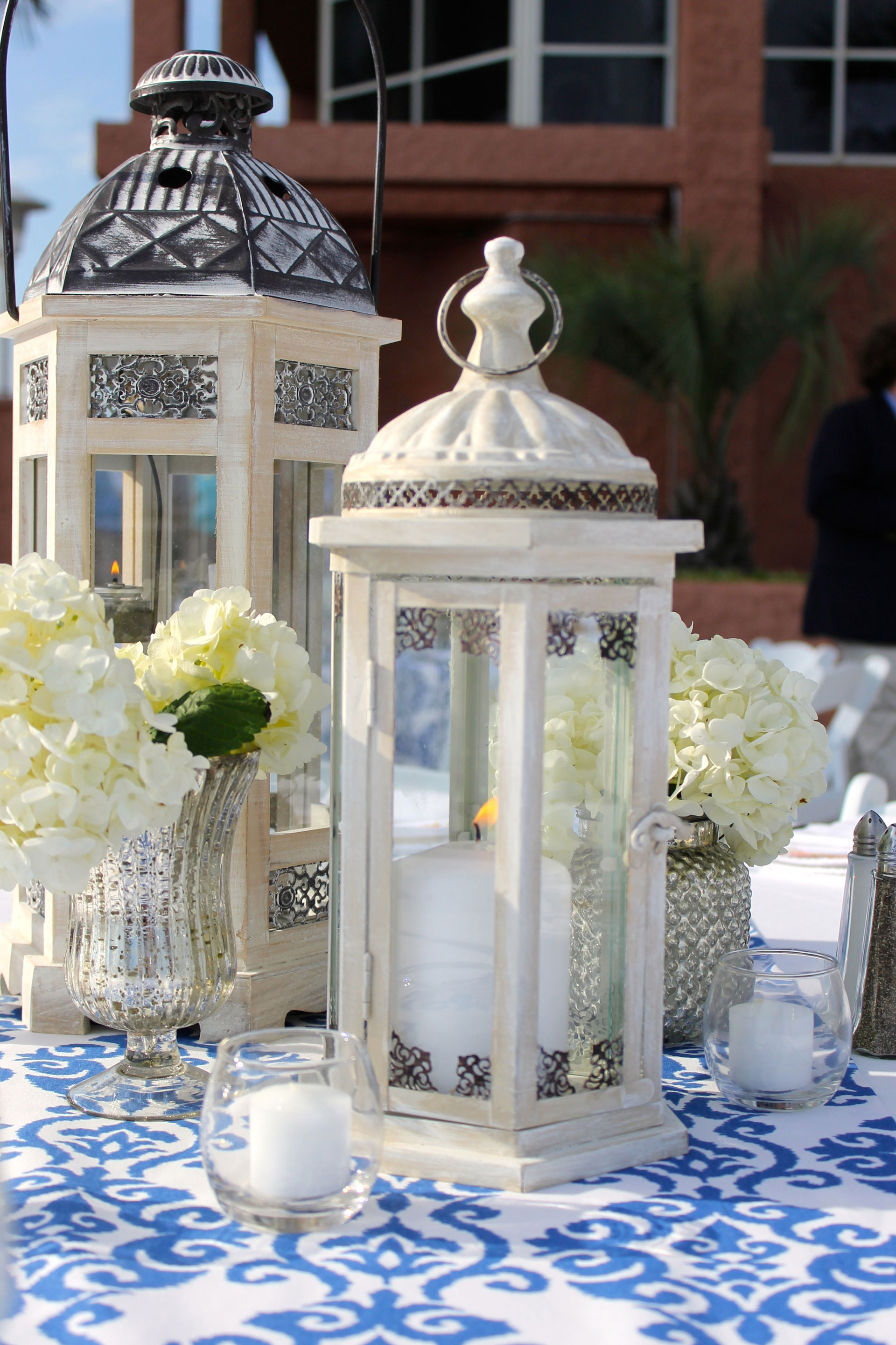 wedding table decor featuring white lanterns with white votive candles