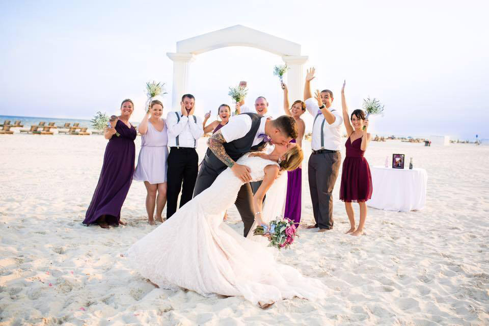 bridal party posing outdoors in front of beach wedding arch