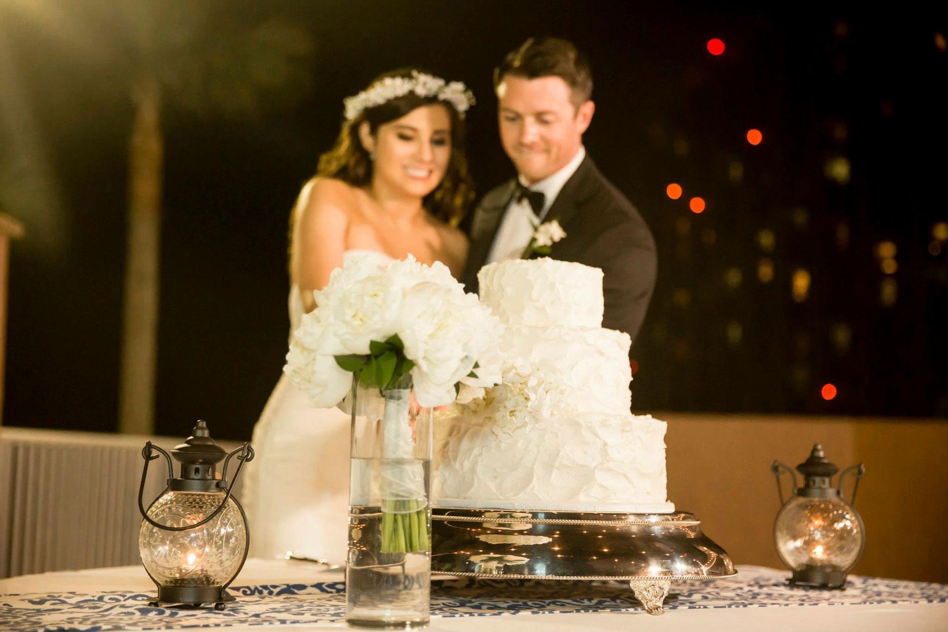 bride and groom cutting wedding cake at night