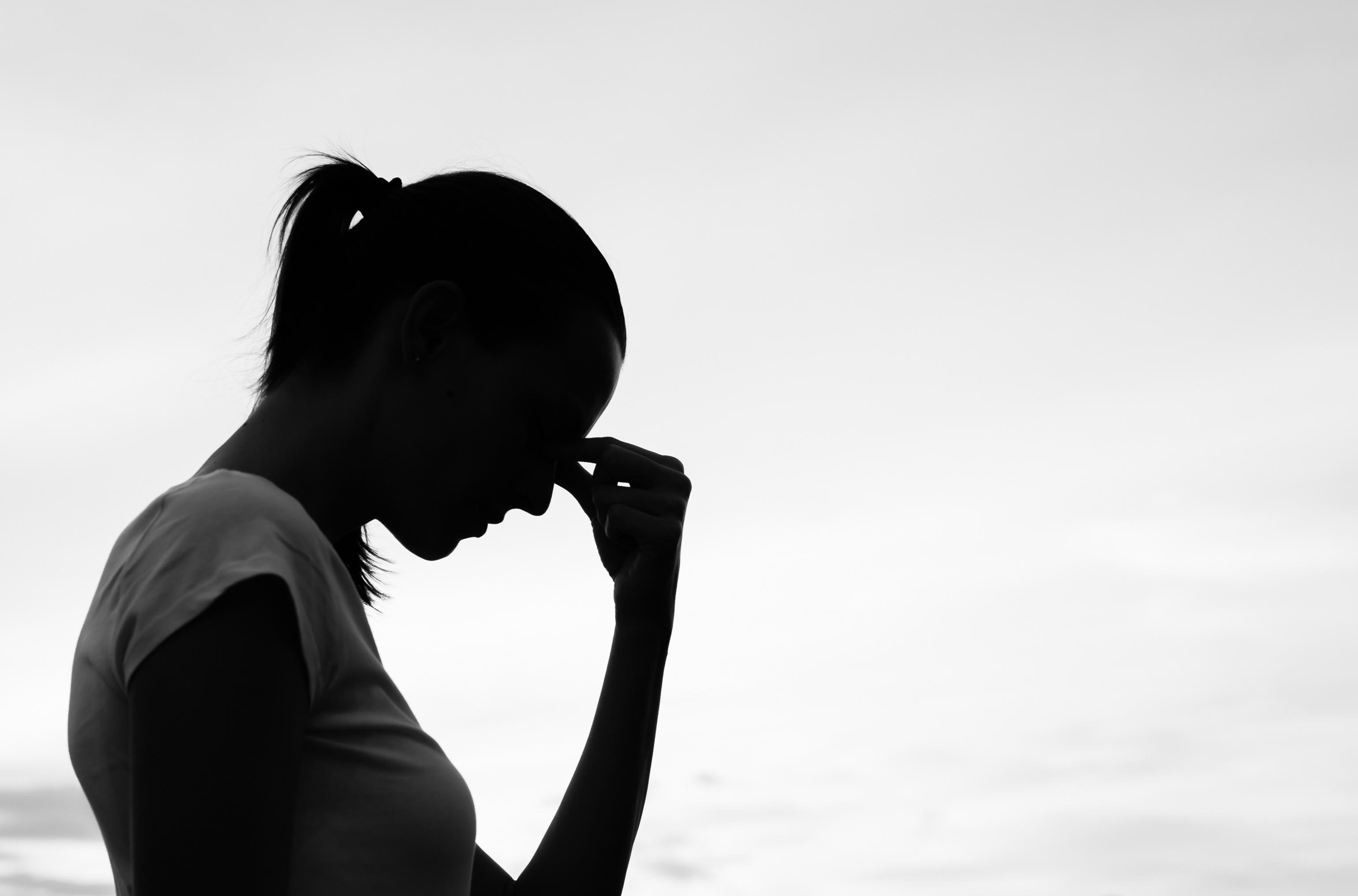 black and white image of woman holding bridge of nose in pain