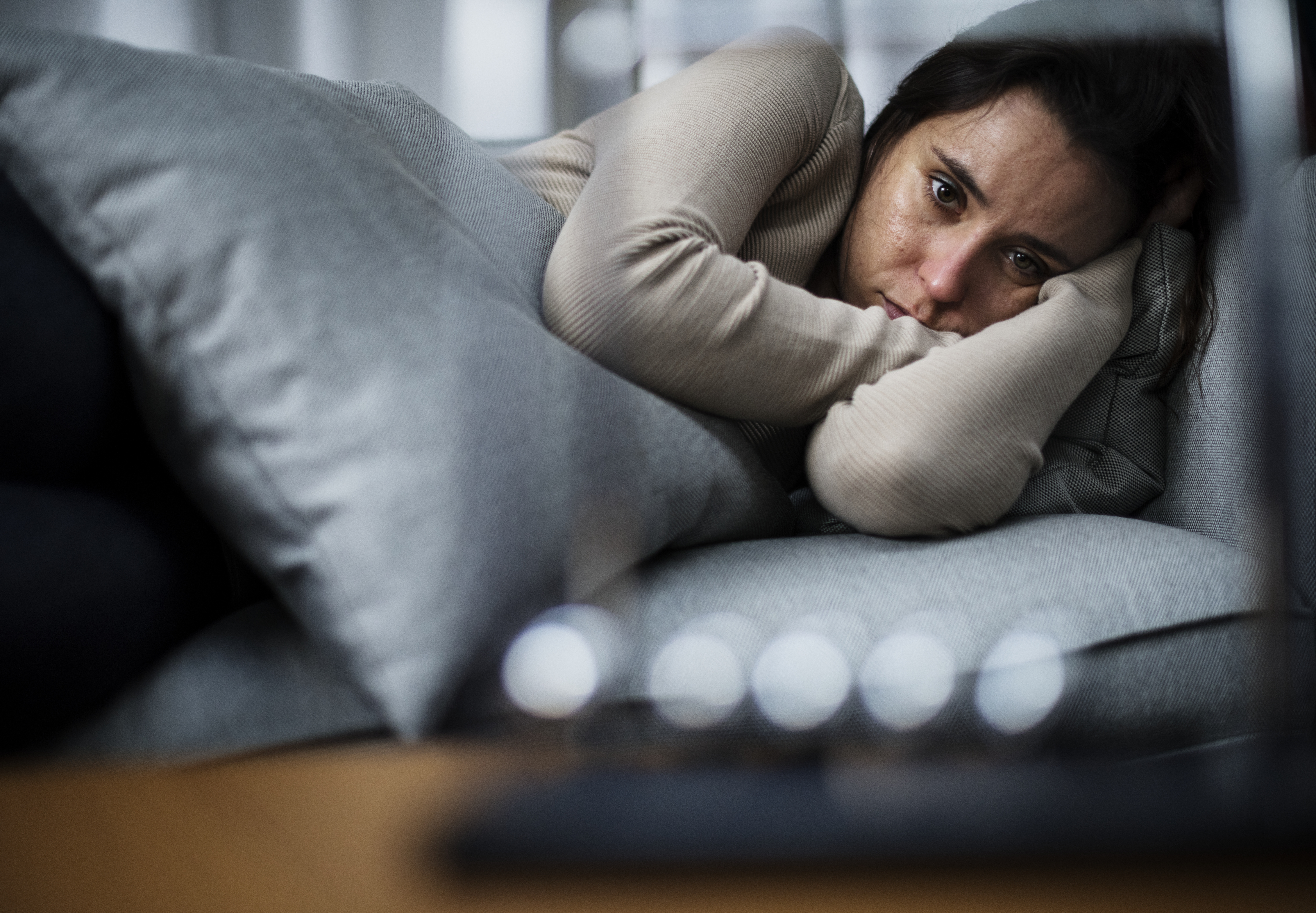 woman curled up on couch looking distraught