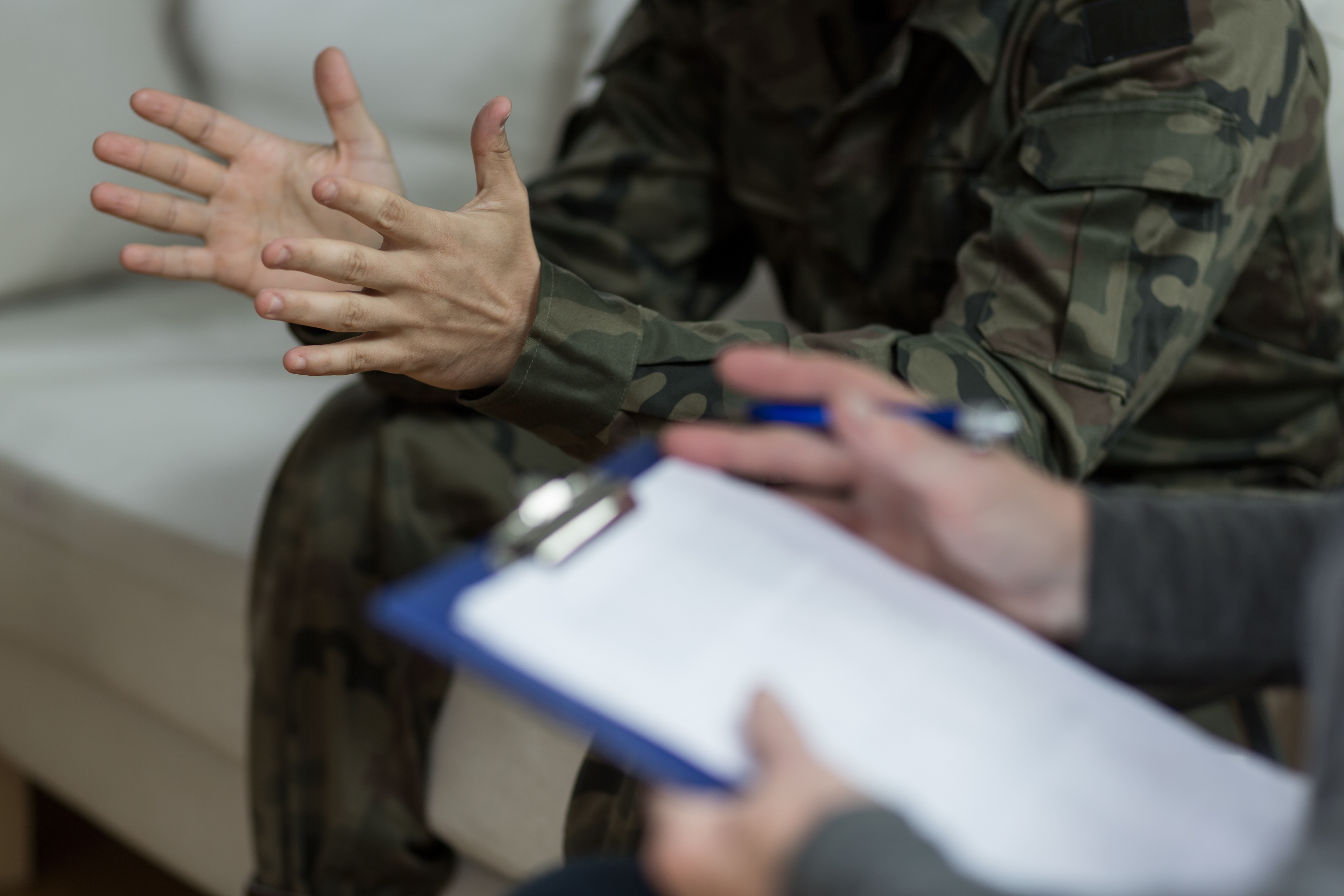 military patient speaking with healthcare professional holding clipboard