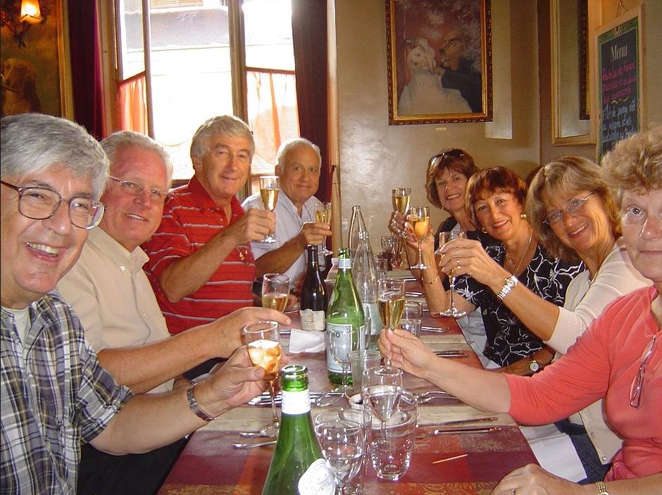 group at a long table cheering and looking at camera
