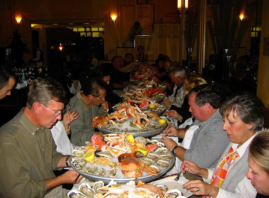 large group dining at a long table on an array of seafood