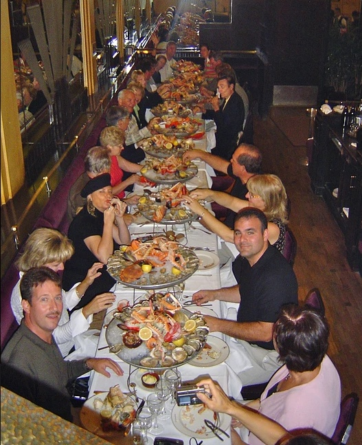 large group dining at a long table on an array of seafood and looking at camera