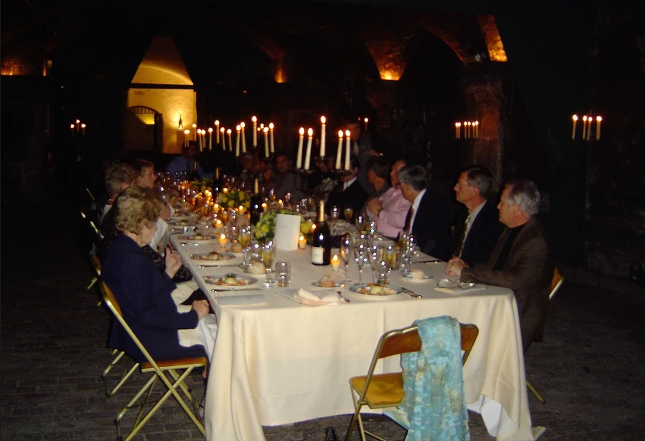 large group of diners at elegant dinner table with candles