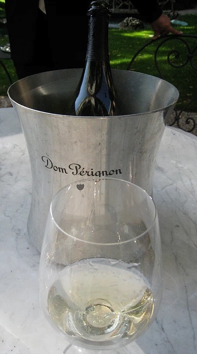 silver Dom Pérignon wine cooler with bottle in it and wine glass in front