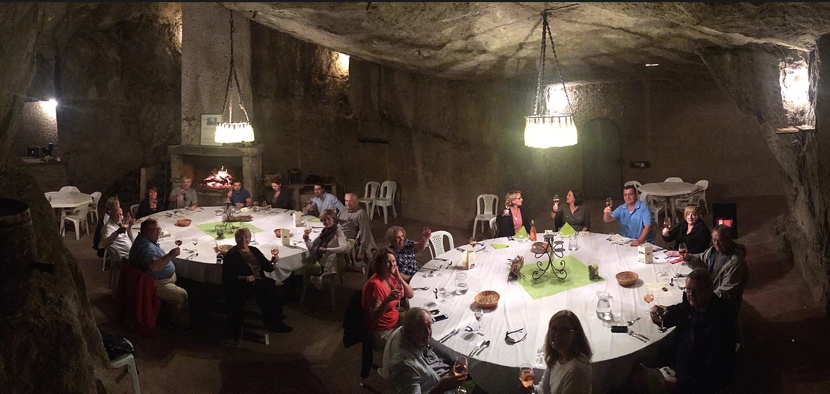 People sitting around 2 large round tables in a dark stone cellar