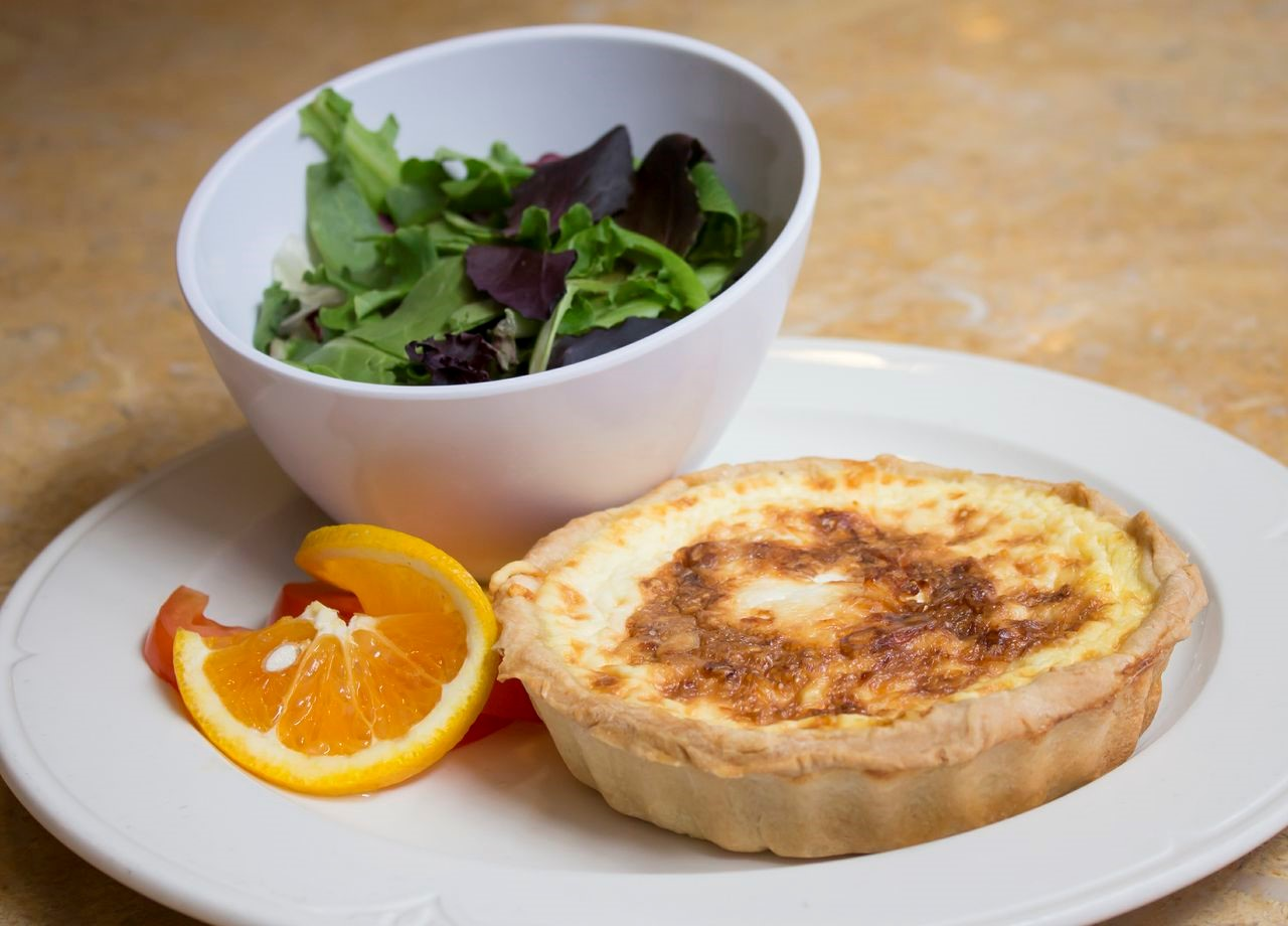 plate with mini-quiche, side salad and a slice of tomato and orange