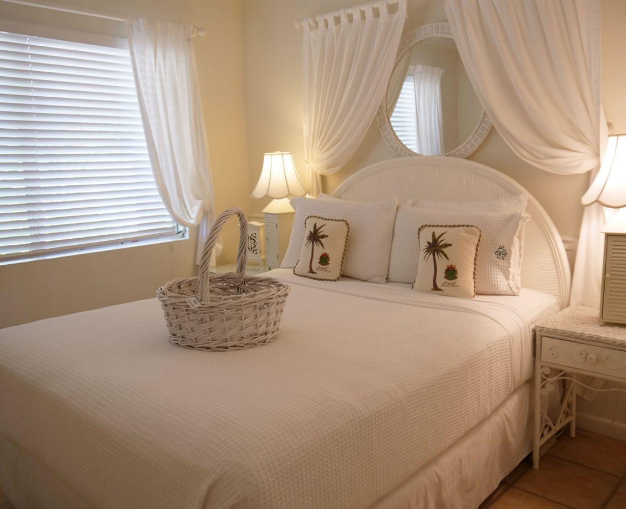 View of queen bed with basket in bedroom