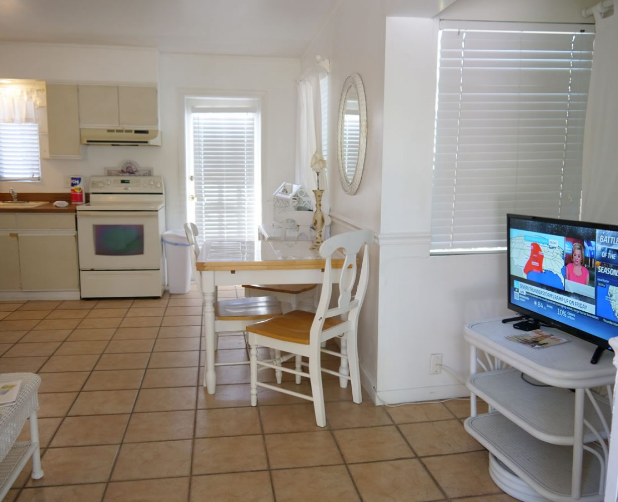 View from t.v. console to dining area, part of the kitchenette and back door