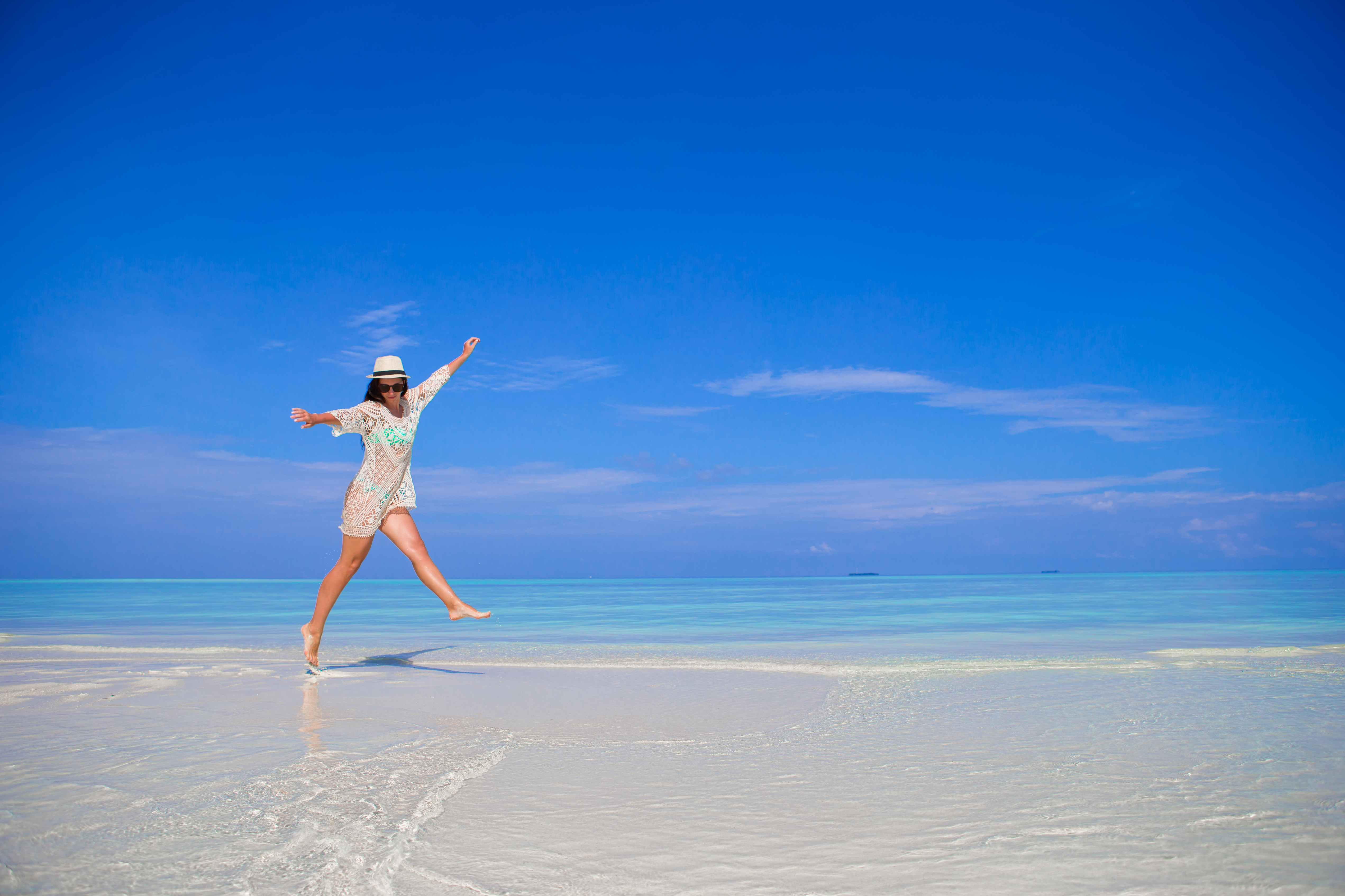 A young woman enjoying a stroll on the white sands of Siesta Key Beach