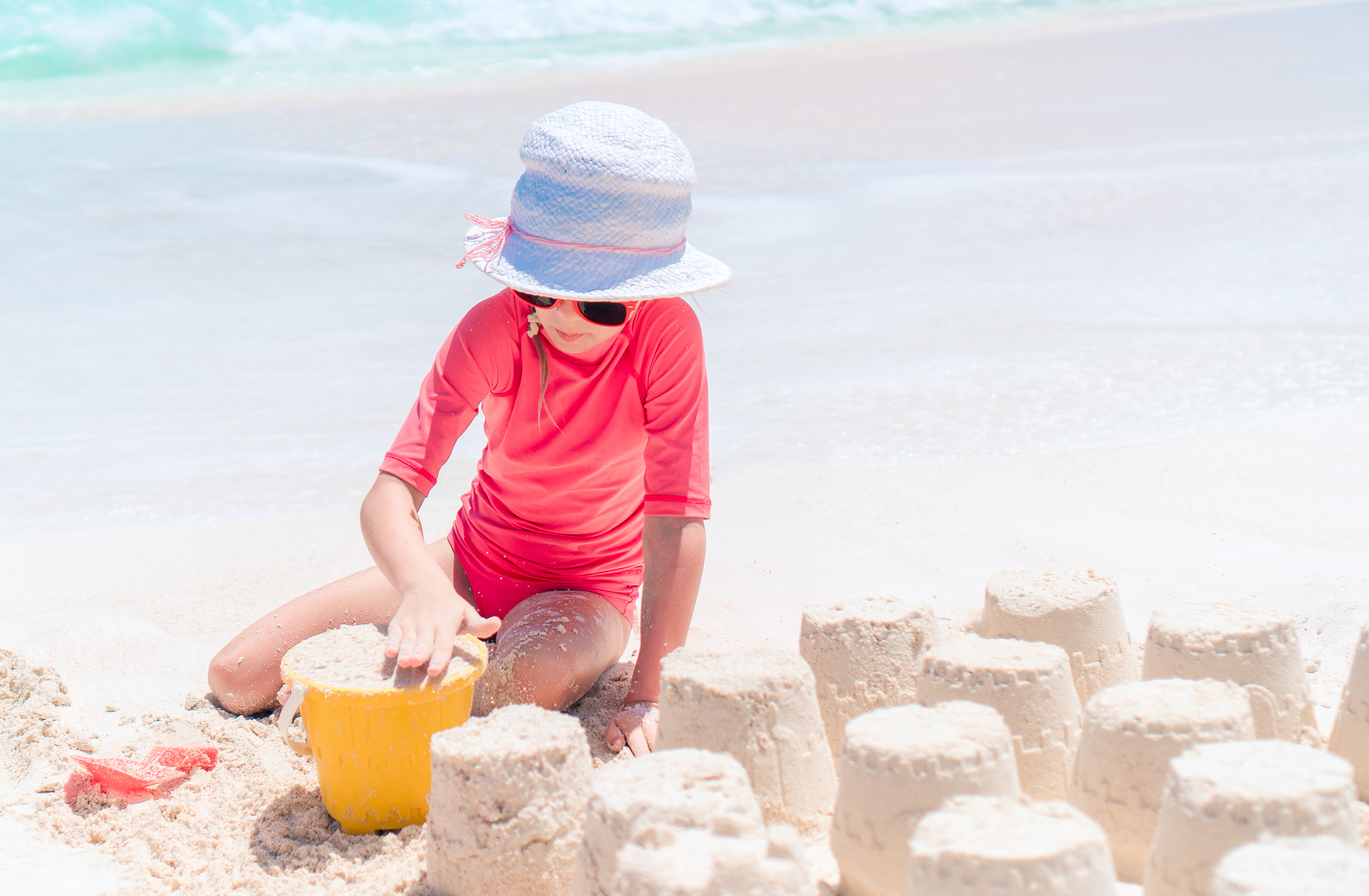 Adorable little girl in hat and sun glasses making sand castles in the white sands of Siesta Key Beach