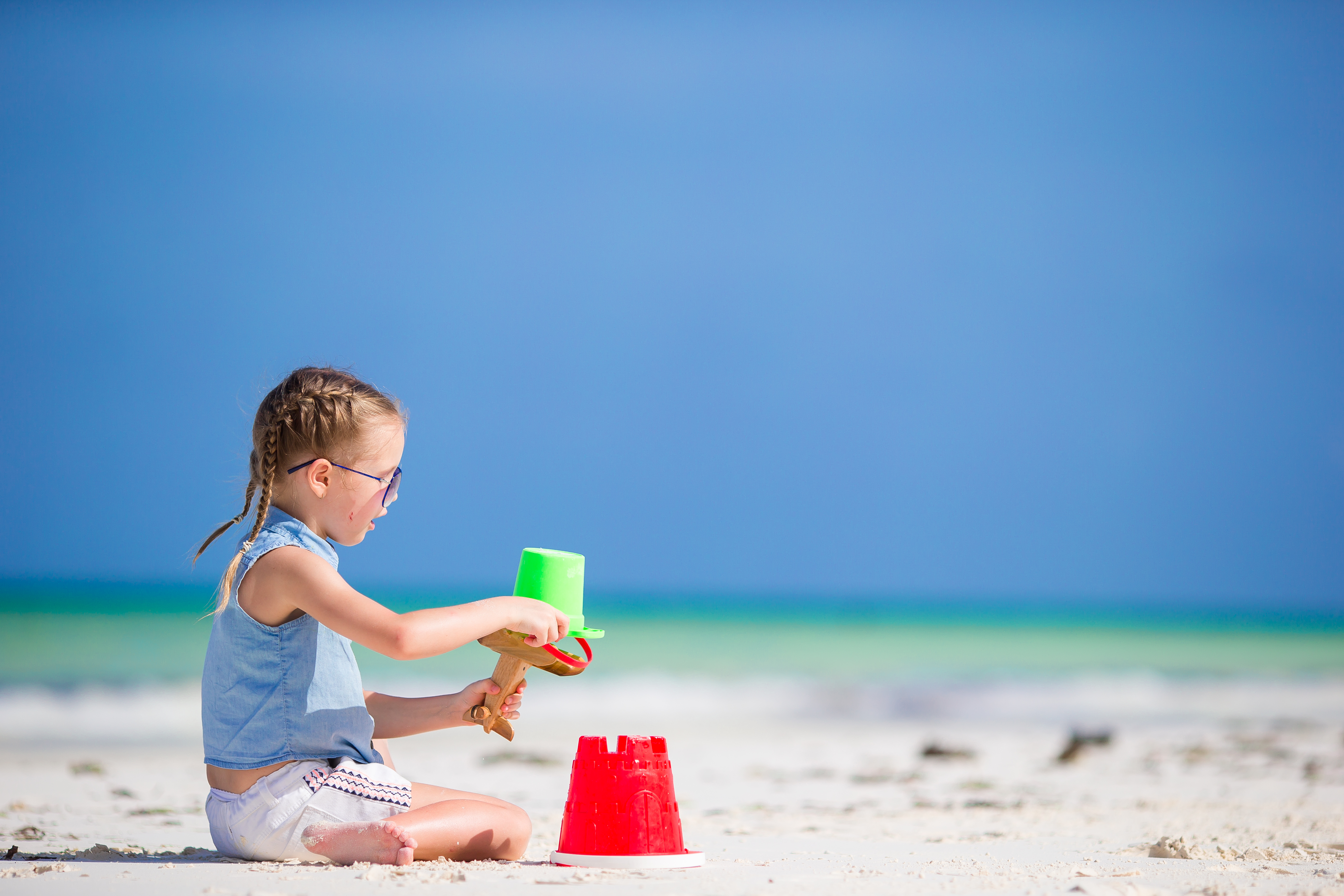 Little girl making a sandcastle while playing in the white sands of Siesta Key