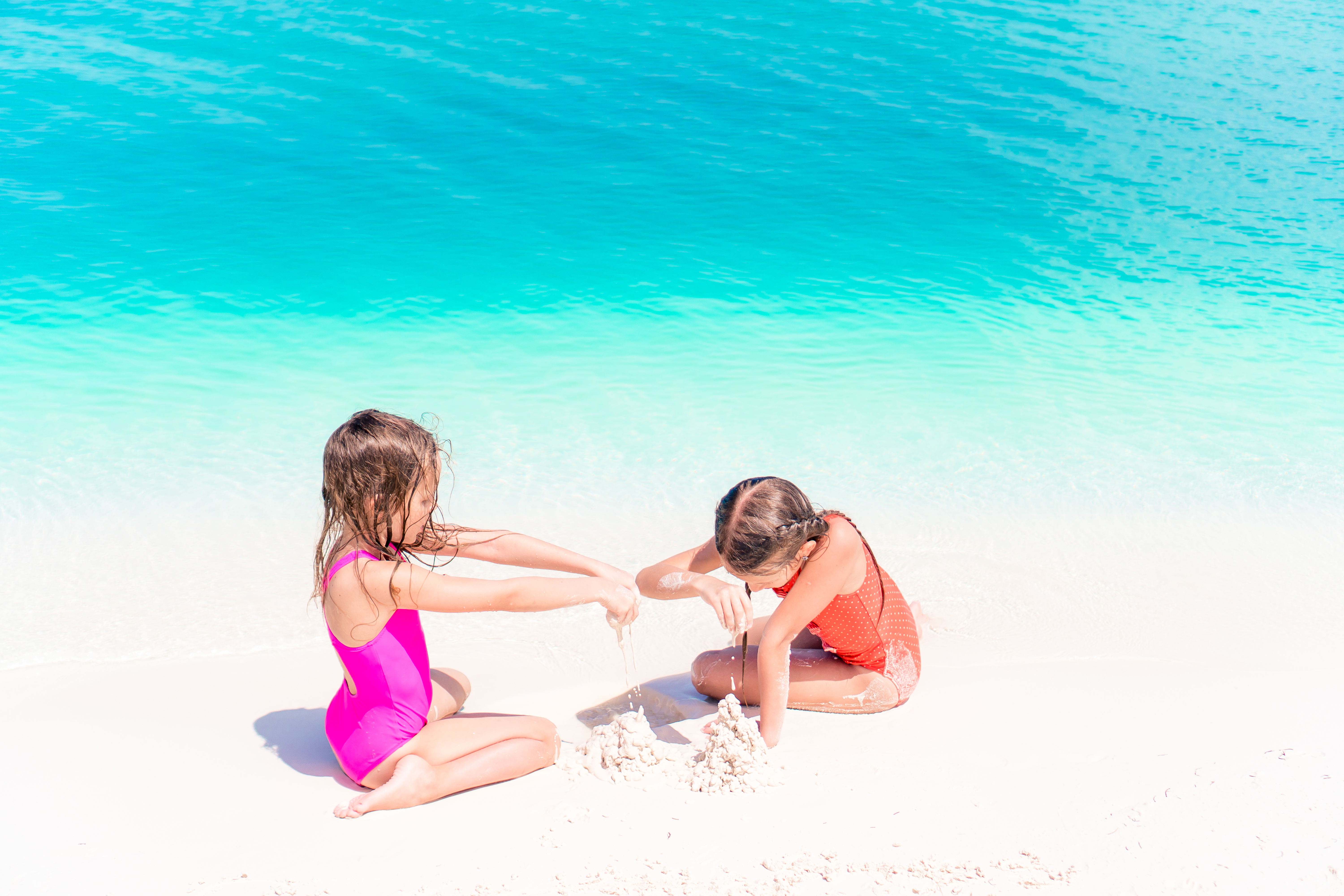 Image of two adorable children playing on the white sand of Siesta Key