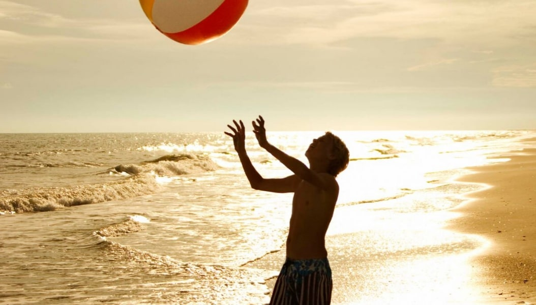 Boy playing with beach ball at sunset on Siesta Key Beach