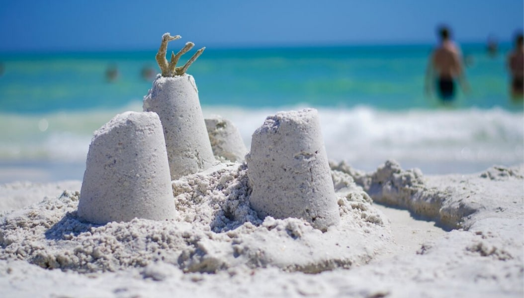 View up close of three small sand castles with beach water in background