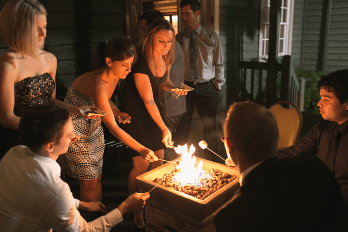 a group of people roasting marshmallows at a social event