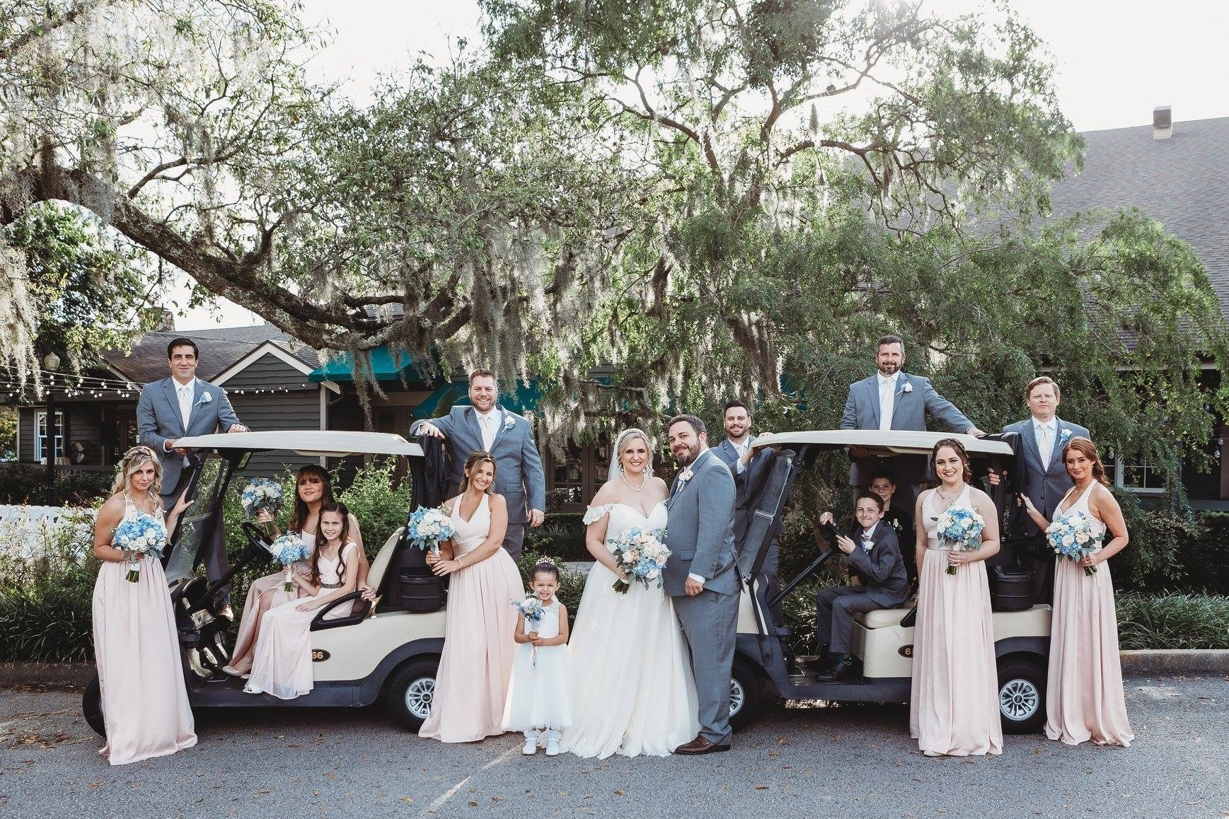 wedding party posing with golf carts