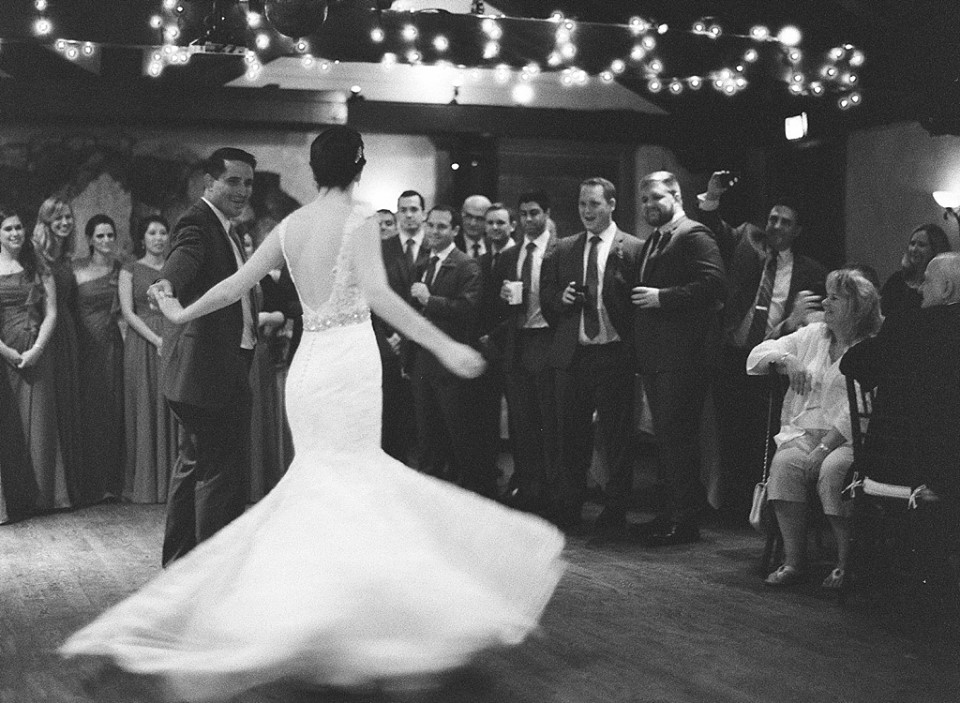 bride's mermaid dress flares out as she dances with groom
