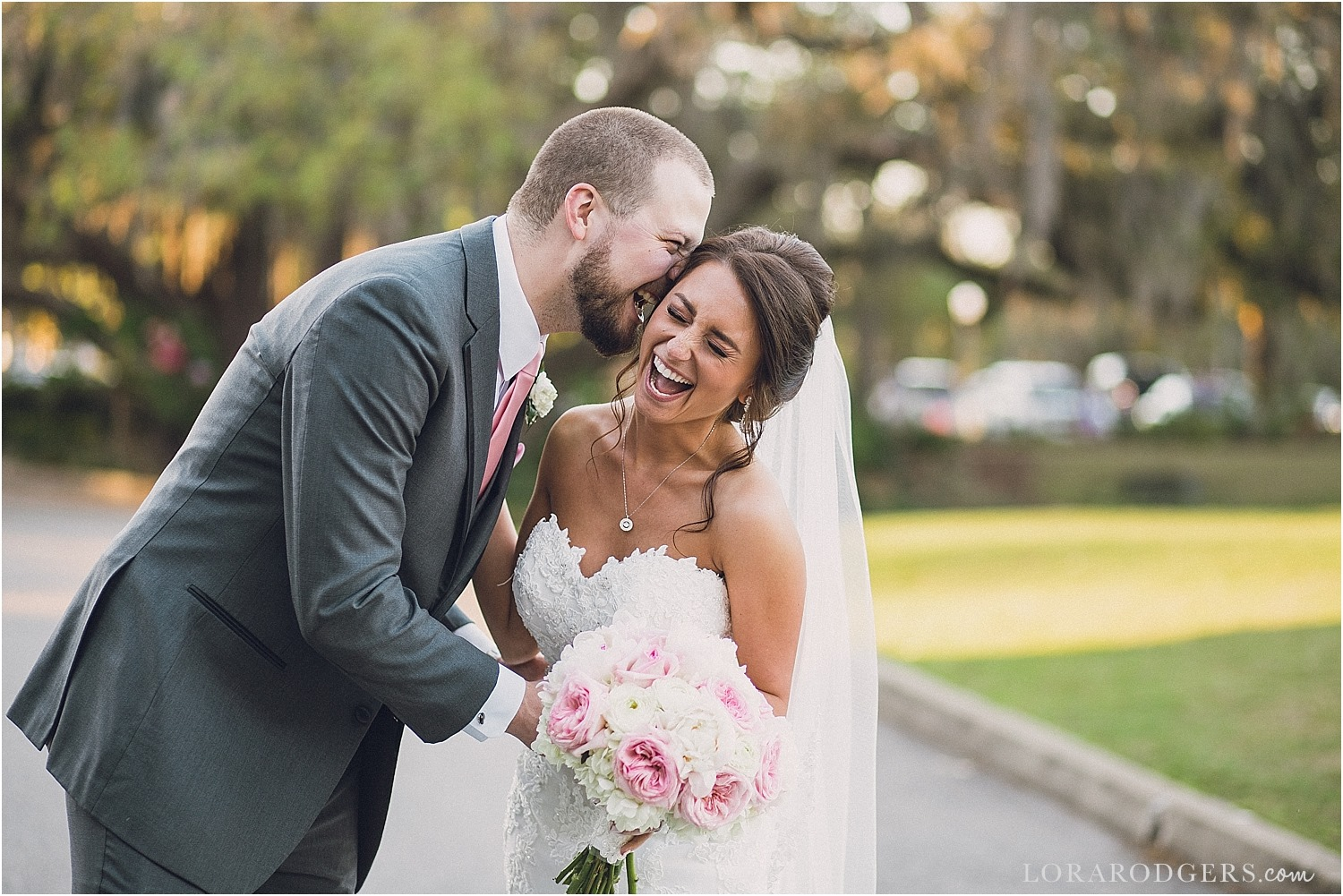 groom whispering in bride's ear as she laughs