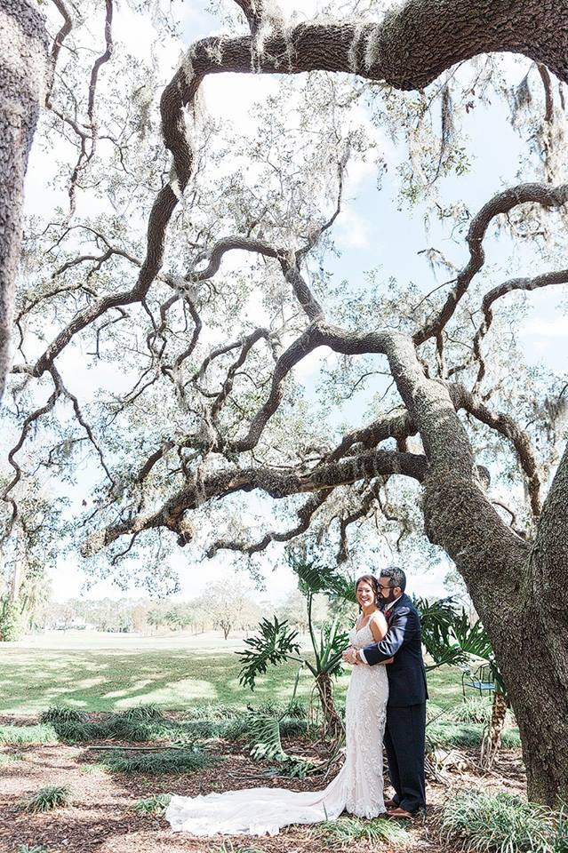 bride and groom pose under tree